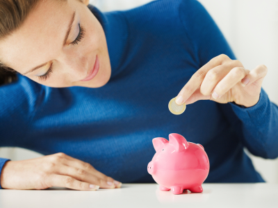 woman putting coins into a piggy bank